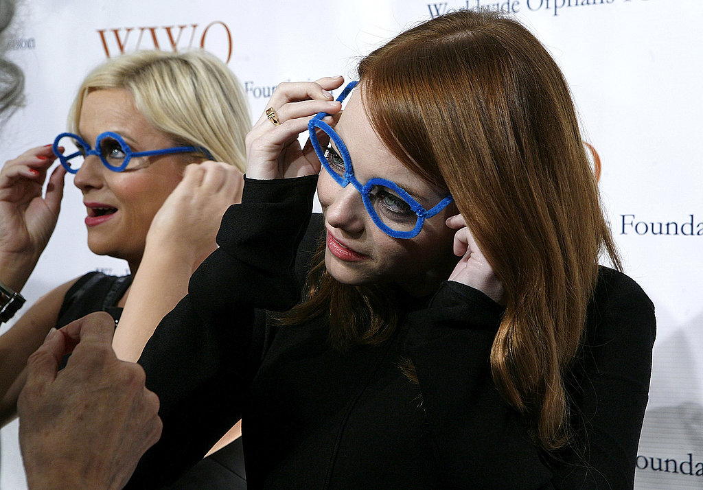 Amy Poehler and Emma Stone put on pairs of pipe-cleaner glasses.