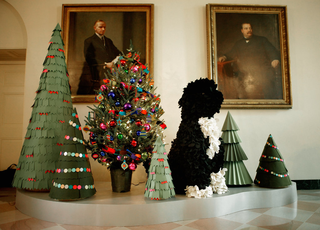 Paper Christmas trees and a felt topiary of the first family's dog, Bo, sit in front of portraits of former Presidents Calvin Coolidge and Grover Cleveland.