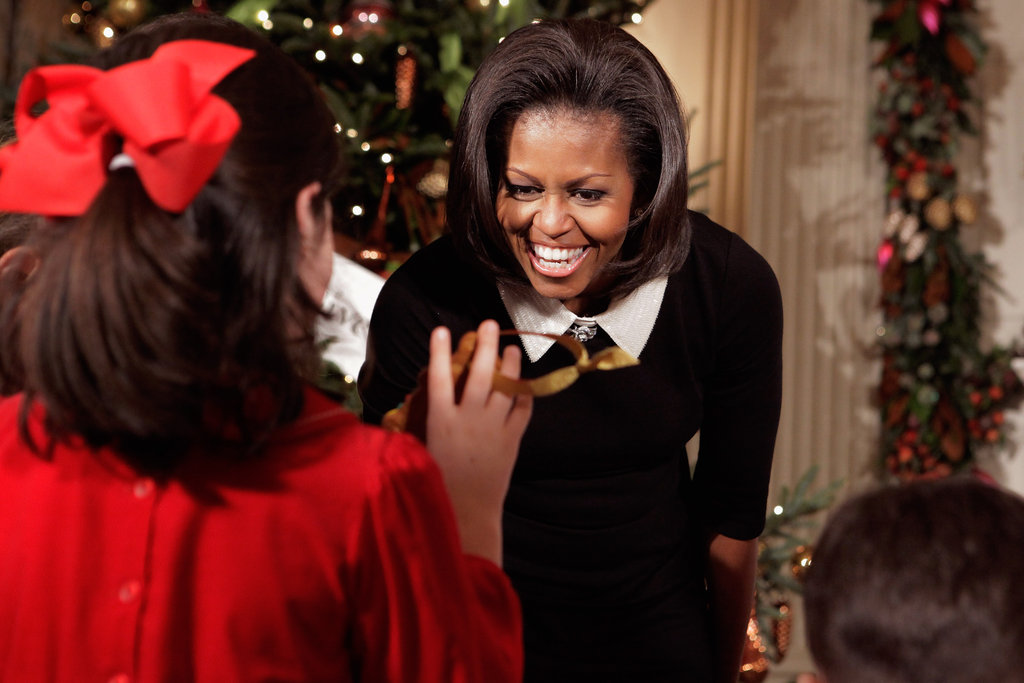 Michelle Obama looks at handmade cookie Christmas ornaments made by children of active duty military service members.