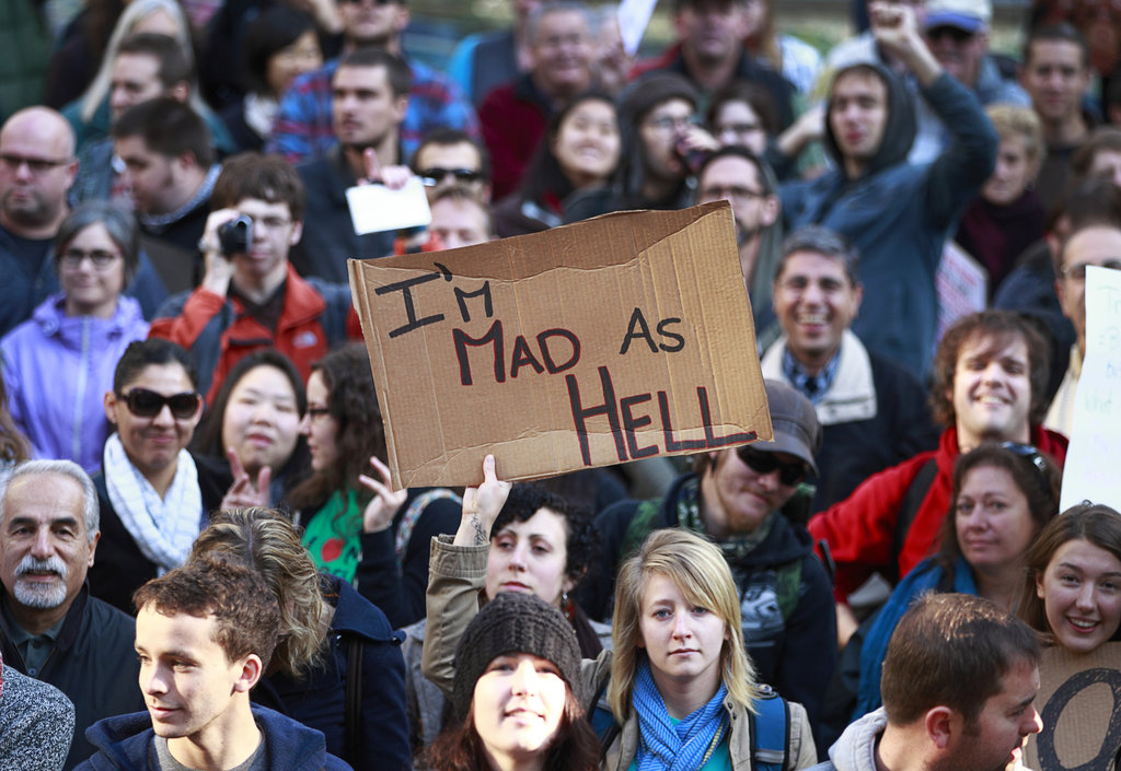 """A woman held up a sign saying """"I'm mad as hell"""" during Occupy Vancouver protest."""