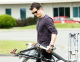 Orlando Bloom carried his bike gear to the car.