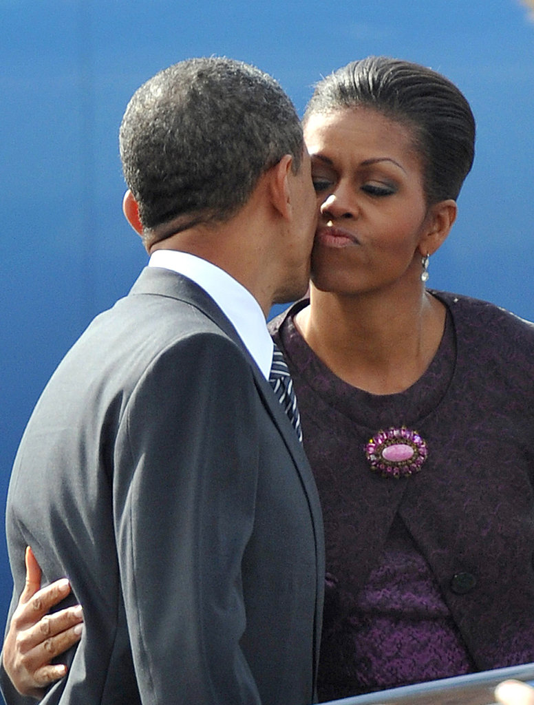 Michelle kisses Barack goodbye in Britain, as she heads back to the US to see their girls.