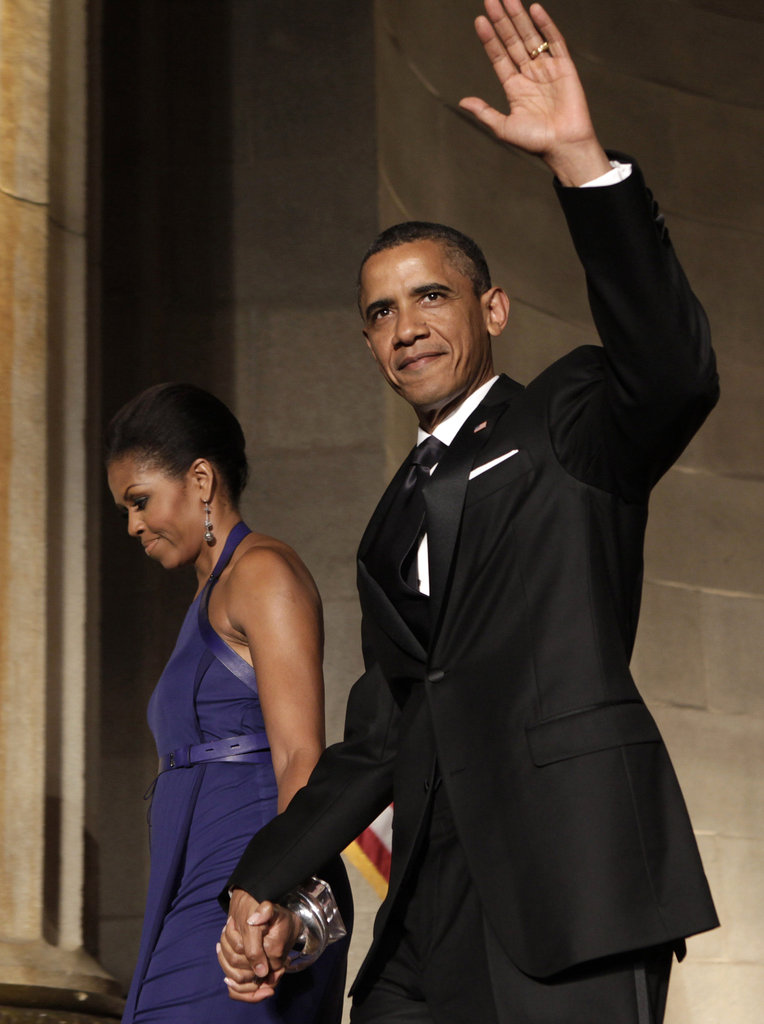 Barack keeps a hold of Michelle's hand as he waves to the crowd at an event in June.
