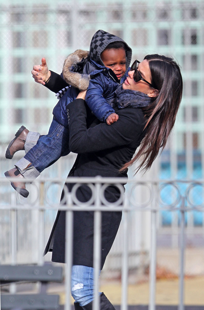 Sandra Bullock holding Louis at a NYC playground.