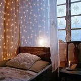 Hang fairy lights between layers of sheer fabric to create a secluded hideaway in your bedroom. Source