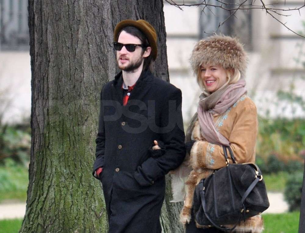 Sienna Miller kept warm with a furry hat and Tom Sturridge.