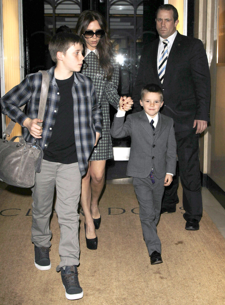 Victoria Beckham held Cruz's hand while heading out of a hotel with Brooklyn.