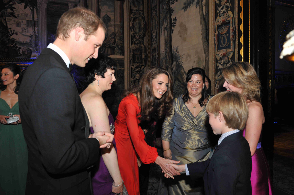 Kate shakes a little boy's hand at a fundraising gala by 100 Women in Hedge Funds, which supports the Child Bereavement Charity at St James's Palace.