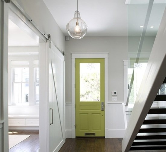 A barn door painted in a coat of glossy white almost pulls off the illusion of a secret sliding wall.   Source