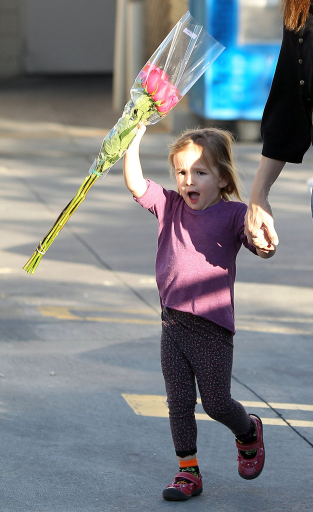Seraphina Affleck skipped with a bouquet of flowers.