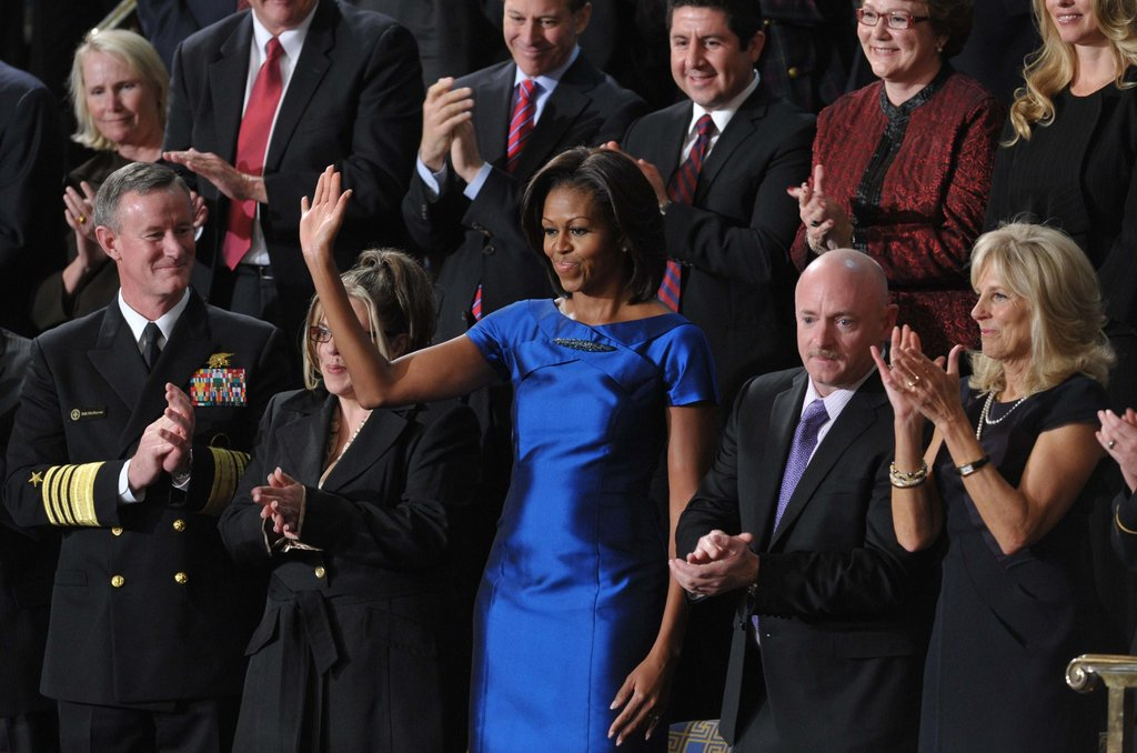 Michelle Obama waves to her husband.