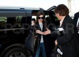 Anne Hathaway smiled at the airport.
