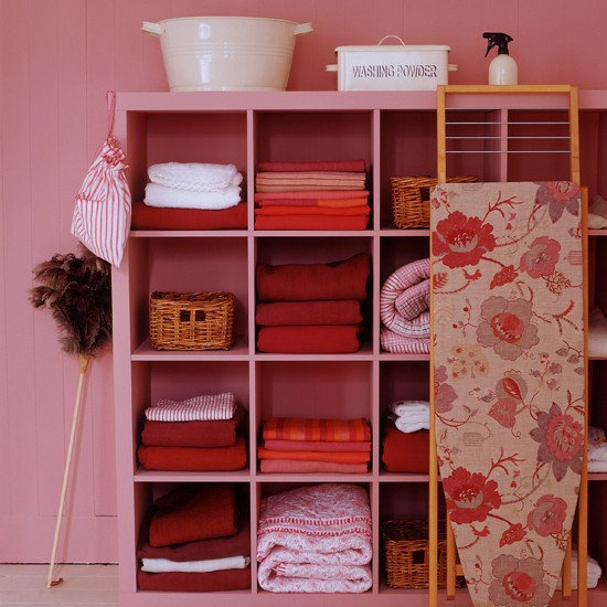Regularly find yourself closing the laundry room door to hide messes? Keep things neat and ready to show off by filling cubed cabinets with matching linens. Paint the walls in a similar shade for a unified look, then brighten the room up using pops of crisp white.  Source