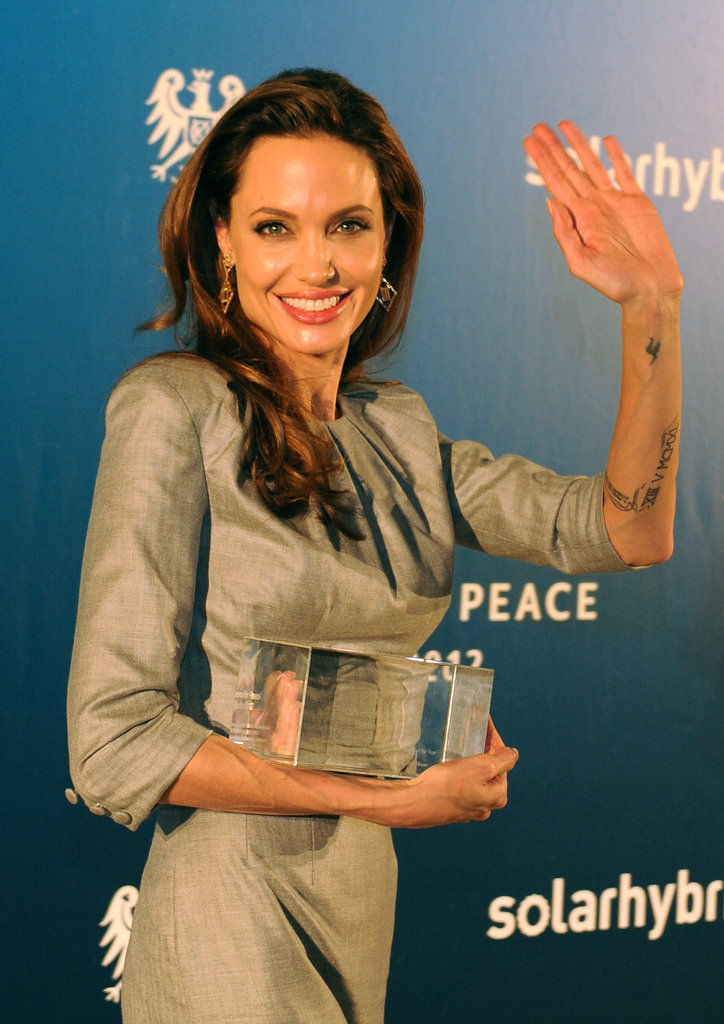 Angelina Jolie waved to photographers as she cradled her honorary Cinema for Peace award.