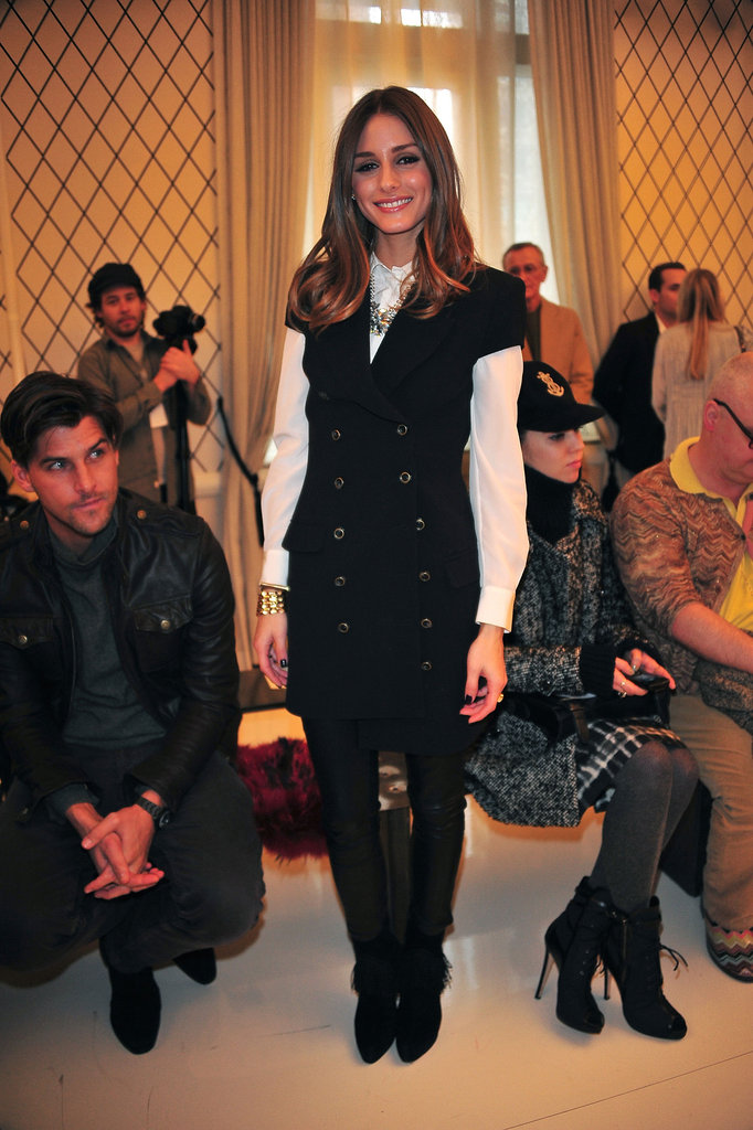 Here, Olivia layered a short-sleeve pea coat dress with a white blouse and leather leggings at the Rachel Zoe presentation.