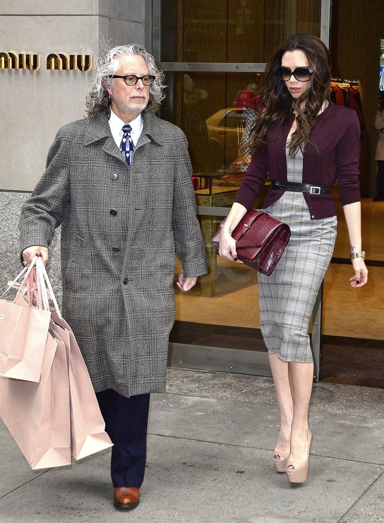 Victoria Beckham left Miu Miu with three pink bags.