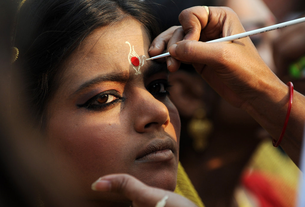 A makeup artist tends to a bride for a mass wedding in Kolkata, India.