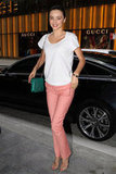 Miranda Kerr kept it sweet with slim pink-hued jeans, a white t-shirt, and a slick green bag.