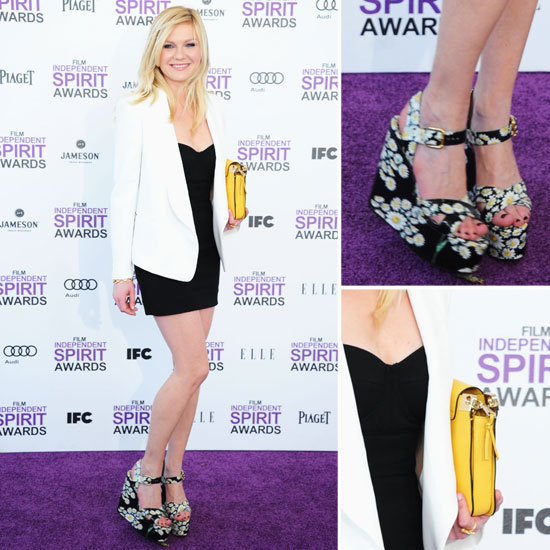 Kirsten Dunst looked chic in a black-and-white Dolce & Gabbana ensemble. She topped her strapless black mini with a cool white blazer. To add some color into the mix, she wore sweet daisy-infused wedges and toted a bright yellow portfolio clutch.