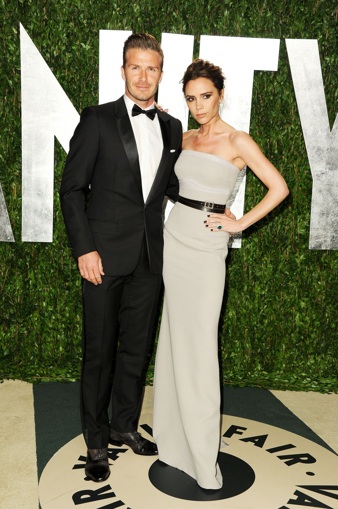 David and Victoria Beckham together. Victoria wore a modern strapless light gray dress from her own collection, styled with a black leather belt.