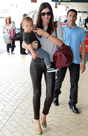 Miranda Kerr dressed down slick leather pants with a striped tee for a chic travel style.