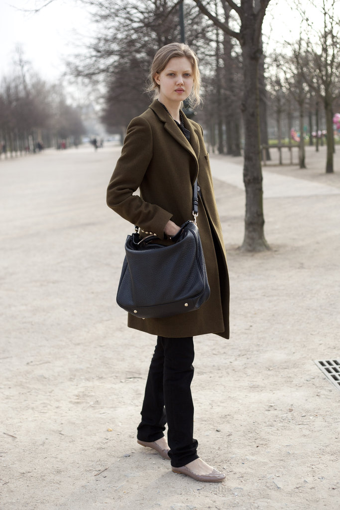 Model Lindsey Wixson pairs scallop-edged nude flats with laid-back add-ons, like a messenger bag and a cozy olive green coat.