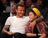 David Beckham with Brooklyn at a basketball game.