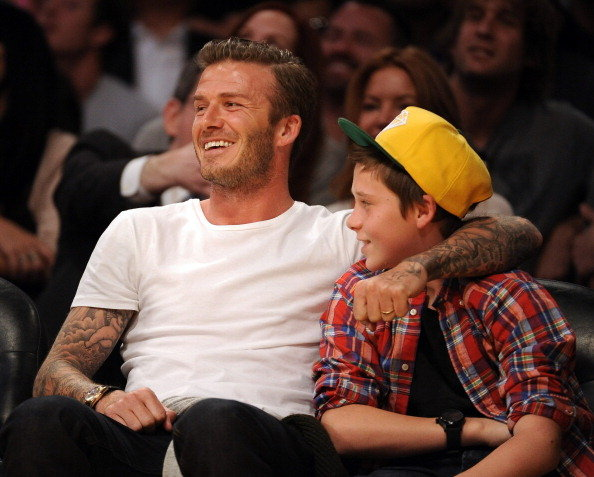 David Beckham with Brooklyn at a basketball game.