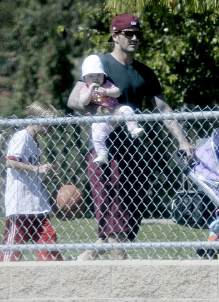 David Beckham holds daughter Harper Beckham with son Romeo Beckham.