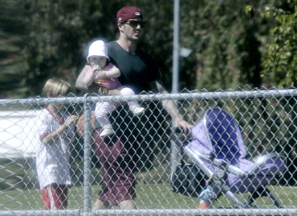 David Beckham holds daughter Harper Beckham at a soccer field.