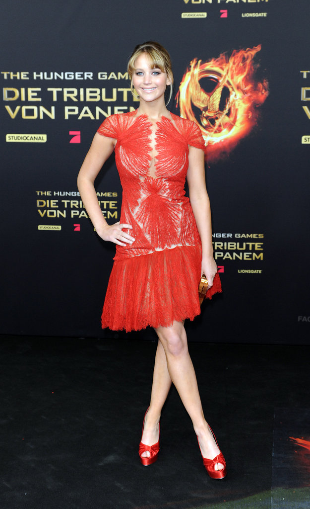 Jennifer Lawrence stepped out for the Berlin premiere of The Hunger Games in a flirty Marchesa dress, red Giuseppe Zanotti heels to match, and a gold Ferragamo clutch in hand — the perfect balance of femininity and sex appeal.