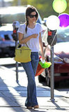 Rachel Bilson kept it simple in easy flares and a white tee — with just a pop of color on her bag.
