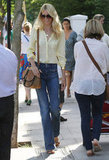 Claudia Schiffer was the picture of style in a soft yellow blouse and high-waist wide-leg denim.