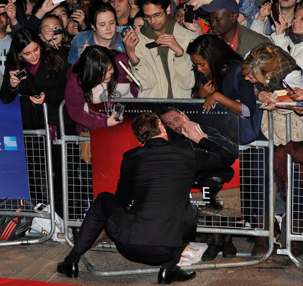 Michael Fassbender gamely signed a picture of himself at an October 2011 London premiere of Shame.