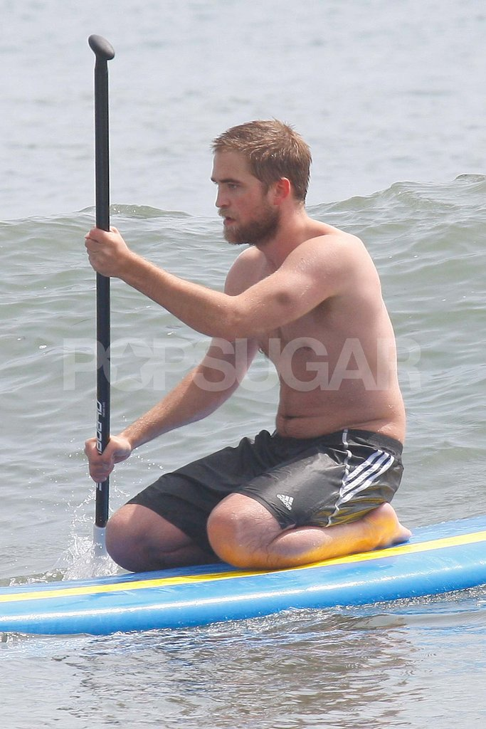 Robert Pattinson sat on a paddleboard.