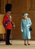 Queen Elizabeth II couldn't help but laugh as she passed her husband at Buckingham Palace in 2005.