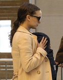 Natalie Portman wore a tan coat and sunglasses through the airport in Paris with baby Aleph in a carrier.