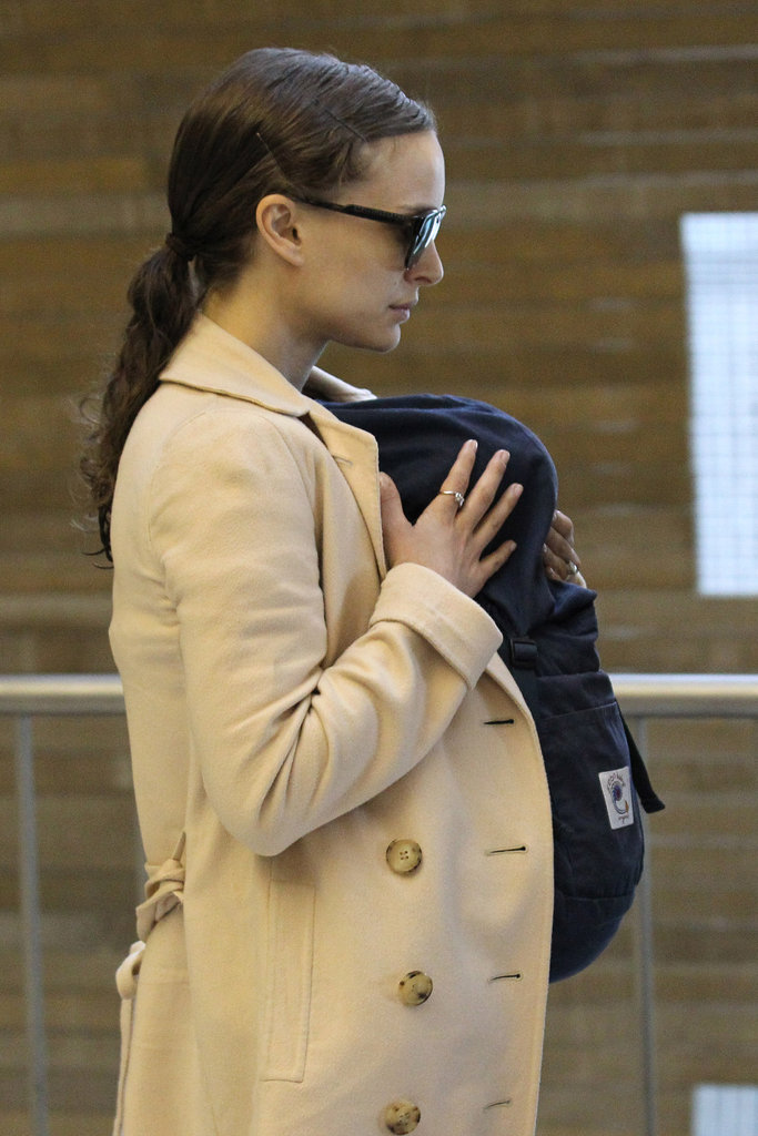 Natalie Portman protected son Aleph in a baby carrier as she made her way through the airport in Paris.