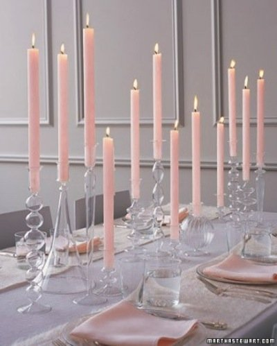 Mix in doses of modernism with a traditional candlelit table using pale pink tapered candles and an assortment of glass holders. The rosy color will cast a warm glow while the glass will help to reflect light.  Source