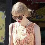 Taylor Swift turns back time, channeling ladylike glamour with tortoiseshell sunglasses and a bold red lip.
