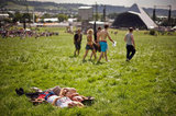 A couple soaked up the sun in the grass at the annual Glastonbury festival in England.