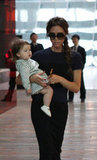 Victoria Beckham carried Harper through the Beijing airport.