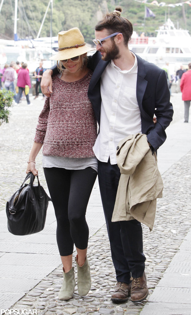 Sienna Miller wore a Rag & Bone sweater and a straw hat as she held onto Tom Sturridge while strolling in Italy.