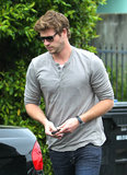 Liam Hemsworth headed to his black sports car.