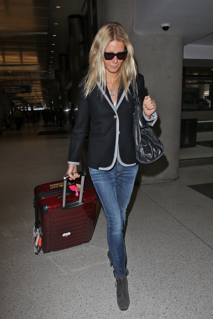 While arriving from London to LA, Gwyneth wore a piped blazer with skinny jeans and her favorite gray suede lace-up booties.  Get her airport-chic look below.  6823233