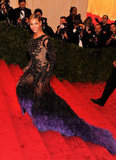 Beyoncé Knowles climbed the stairs at the Met Gala wearing a sheer Givenchy gown with indigo feathers.