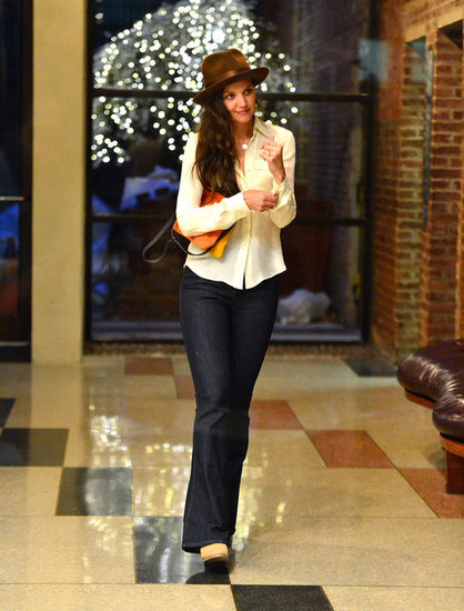 Katie Holmes wore a brown wide-brimmed hat with a white button-down and flared jeans. She accessorized with a colorbluck clutch.