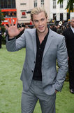 Chris Hemsworth waved to fans in a gray suit.