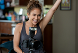Jennifer behind the camera in a dark gray tank and round stud earrings.  6895935