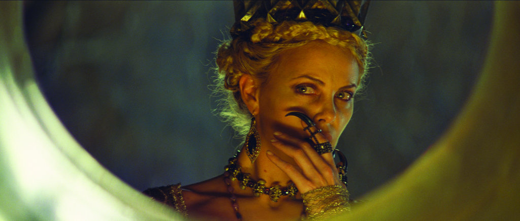 Perhaps wondering if she really is the fairest of all, Ravenna peeks in her looking glass, with claw hook firmly on her finger.  Photo courtesy of Universal Pictures